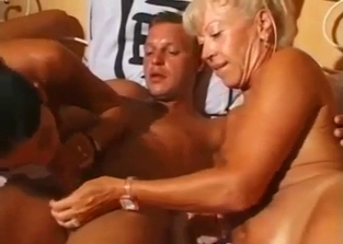Tanned MILF helps her daughter with her son's cock